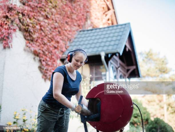 Smiling woman using a electric saw outdoor.