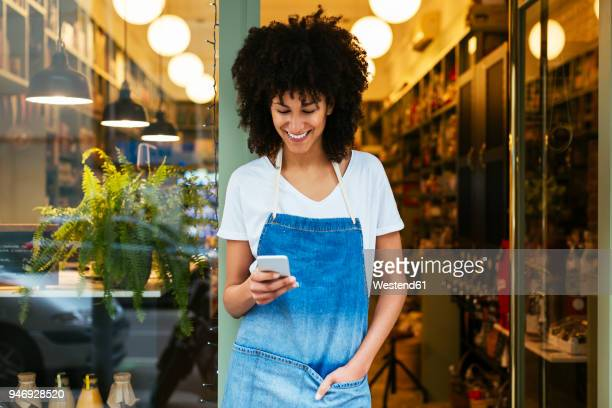 Smiling woman using cell phone in entrance door of a store