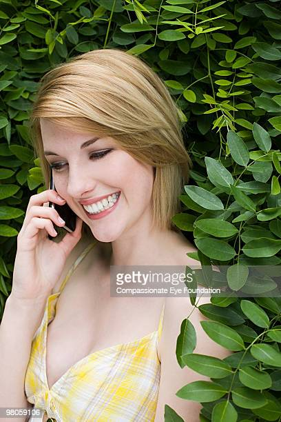 smiling woman using cell phone outdoors - compassionate eye foundation stock pictures, royalty-free photos & images