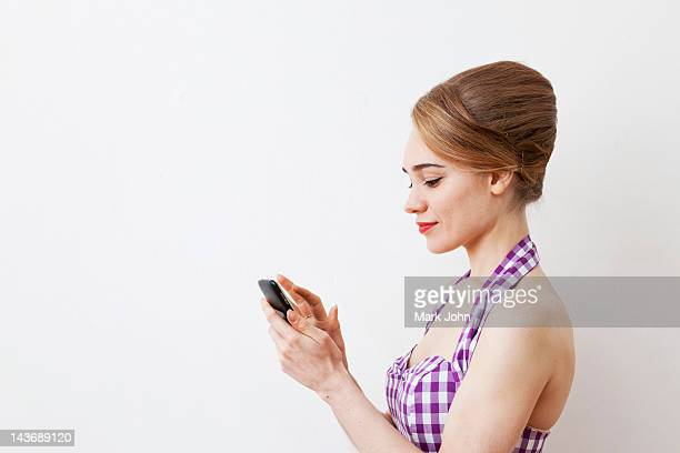smiling woman using cell phone - beehive hair stock photos and pictures
