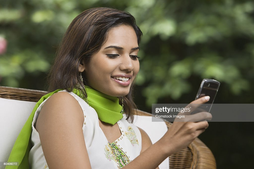 Smiling woman using cellular phone : Stock Photo