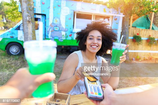 Smiling woman using credit card outdoors