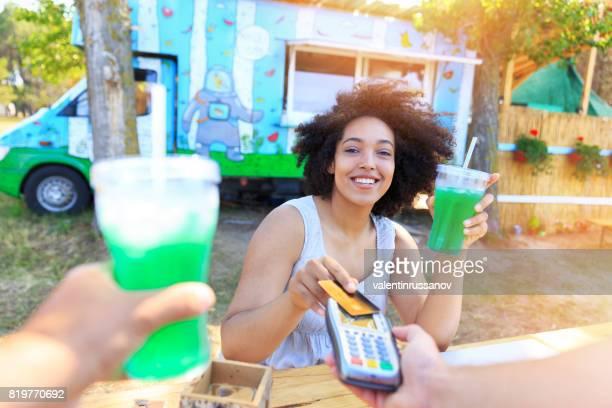 Femme souriante, à l'aide de carte de crédit à l'extérieur