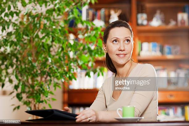 Smiling woman using Digital Tablet and drinking coffee at home