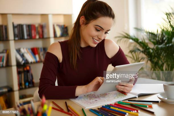smiling woman using digital tablet at home - colouring book stock photos and pictures