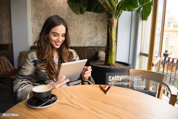smiling woman using digital tablet at the bar - making a reservation stock photos and pictures