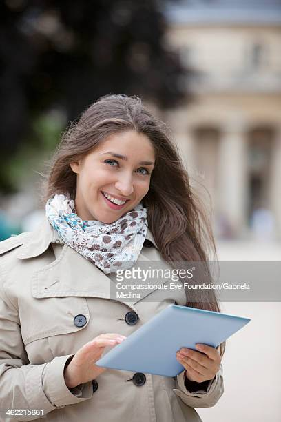"""smiling woman using digital tablet on city street - """"compassionate eye"""" stock pictures, royalty-free photos & images"""