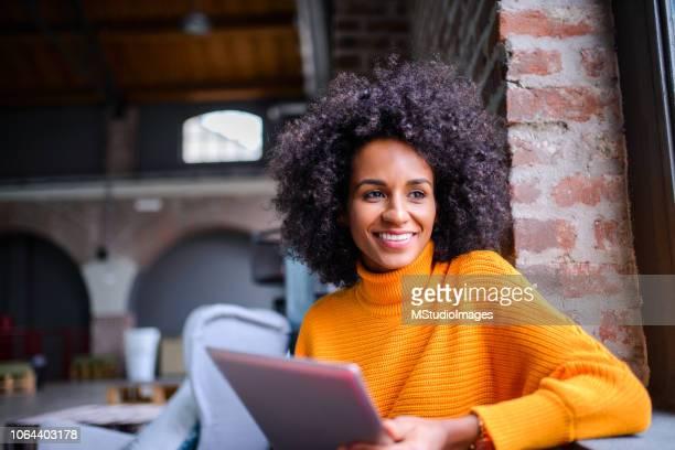mulher sorridente usando tablet digital. - consumismo - fotografias e filmes do acervo