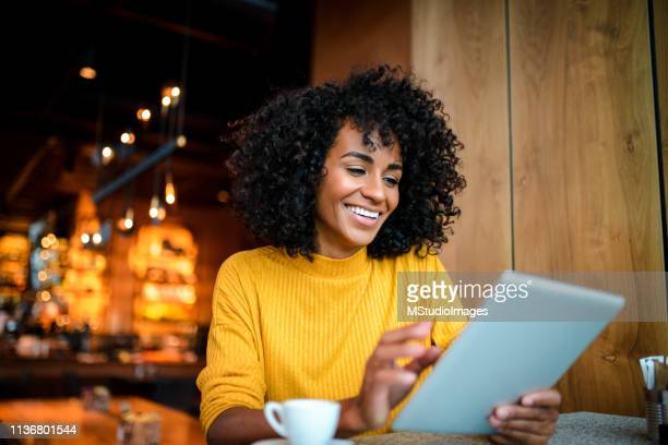 smiling woman using digital tablet. - yellow stock pictures, royalty-free photos & images