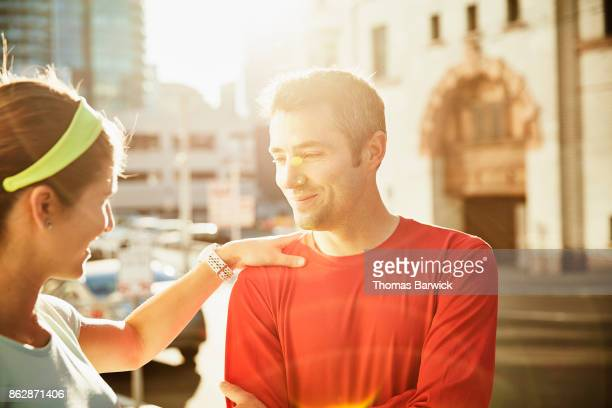 Smiling woman using husband for balance while stretching before early morning run in city