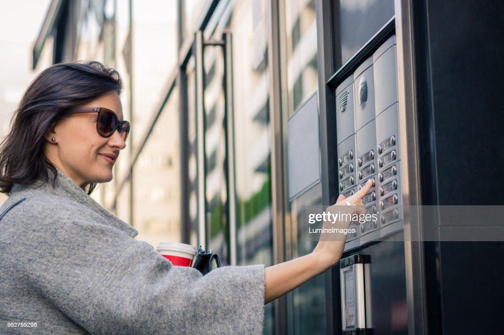 Lächelnde Frau mit Sprechanlage am Eingang bauen. : Stock-Foto