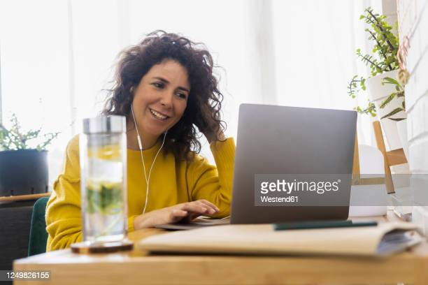smiling woman using laptop at desk in home office - brown hair stock pictures, royalty-free photos & images