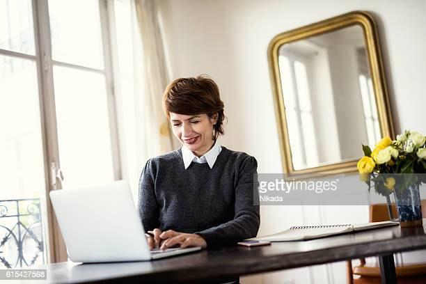 Smiling woman using laptop at table by window