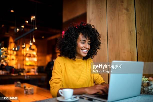 smiling woman using laptop at the bar. - computer foto e immagini stock