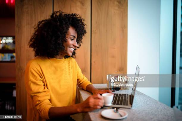 smiling woman using laptop at the bar. - science and technology stock pictures, royalty-free photos & images
