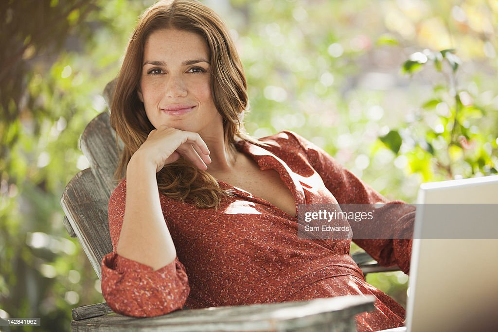 Smiling woman using laptop outdoors : Bildbanksbilder