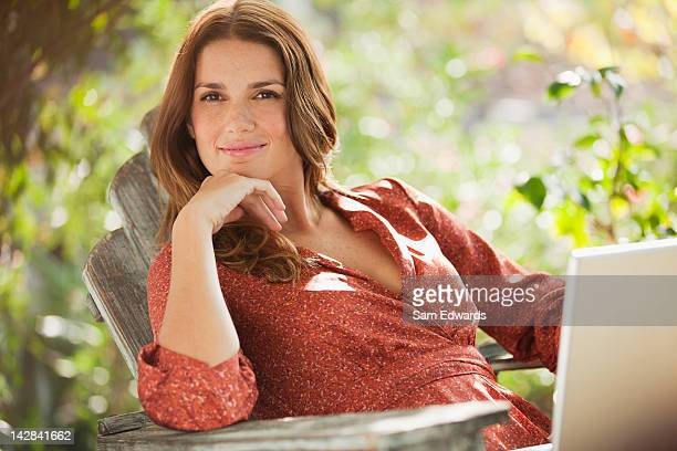 smiling woman using laptop outdoors - one mid adult woman only stock pictures, royalty-free photos & images