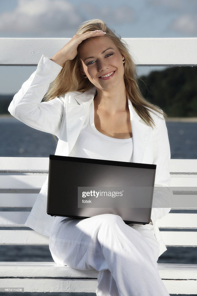 Smiling woman using laptop outdoors : Stock Photo