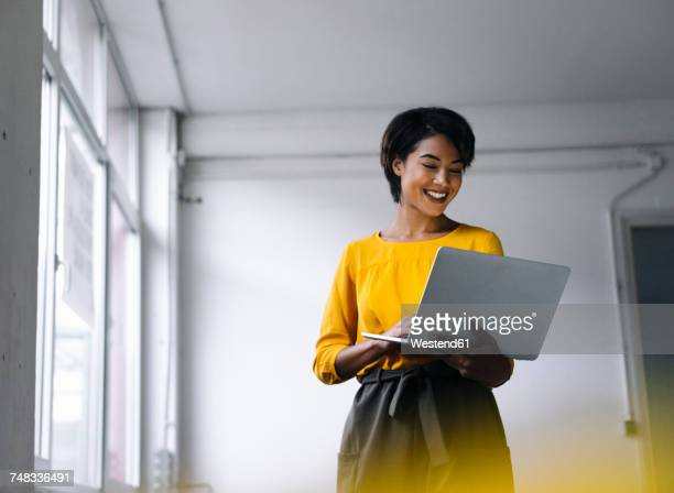 smiling woman using laptop - yellow photos et images de collection