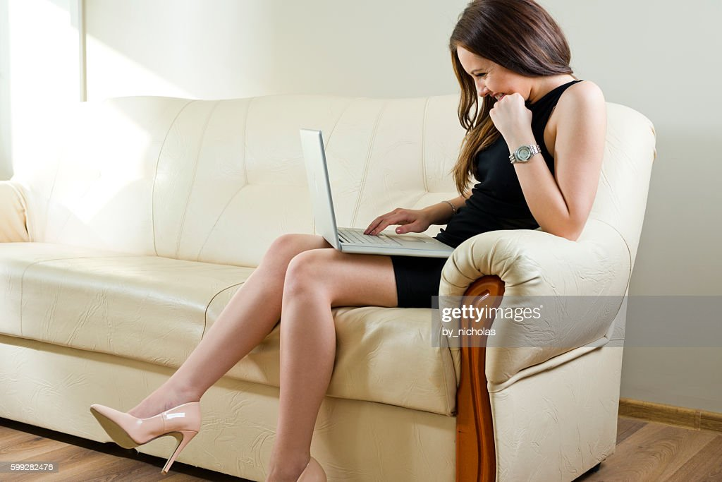 Smiling woman using laptop sitting on the sofa : Stock Photo