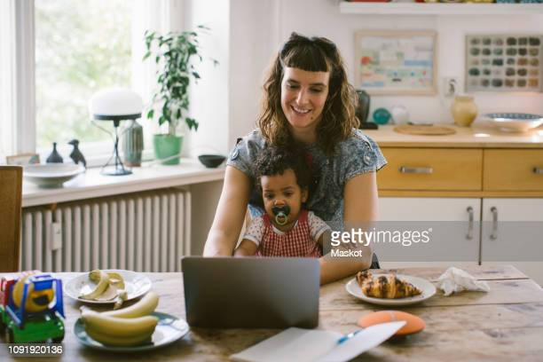smiling woman using laptop while sitting with daughter at dining table in house - alleenstaande moeder stockfoto's en -beelden