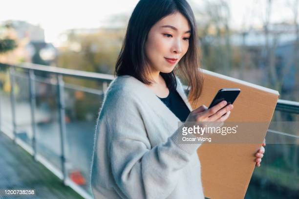 smiling woman using mobile app with smartphone to arrange a delivery - sending stock pictures, royalty-free photos & images