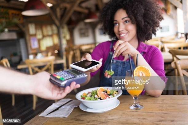 Smiling woman using mobile payment in restaurant