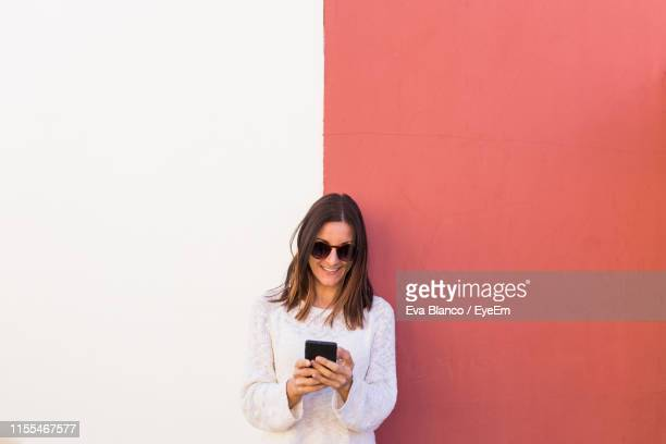 smiling woman using mobile phone against wall - portability stock pictures, royalty-free photos & images