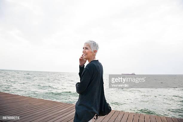 Mujer sonriente mediante teléfono móvil