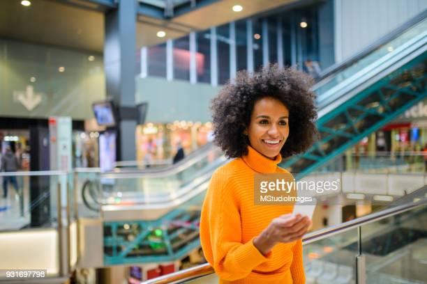 Smiling woman using mobile phone.