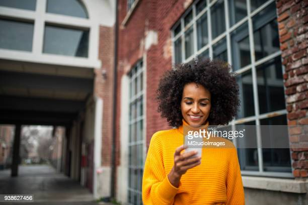 Smiling woman using mobile phone.
