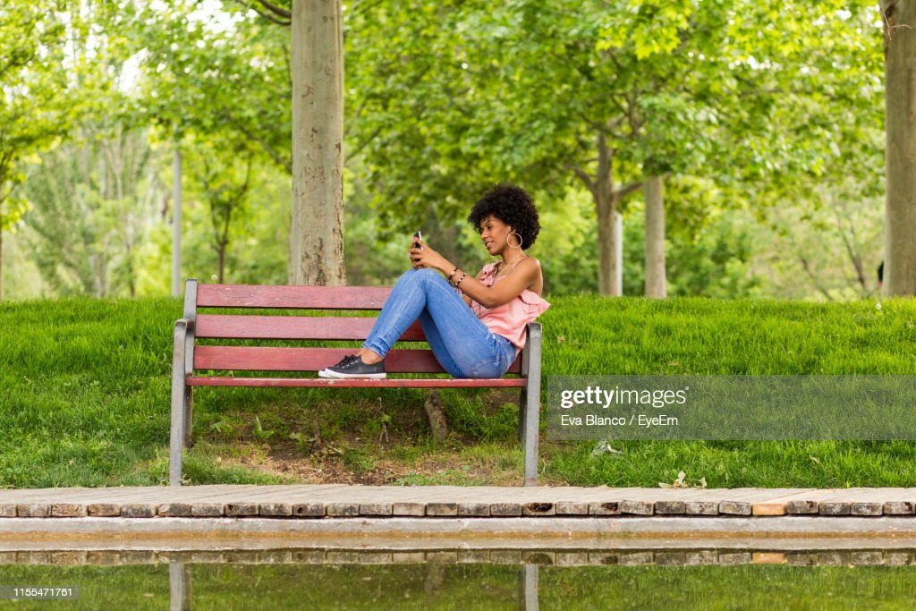 Swell Smiling Woman Using Mobile Phone While Sitting On Wooden Ocoug Best Dining Table And Chair Ideas Images Ocougorg
