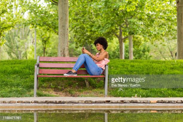 smiling woman using mobile phone while sitting on wooden bench at park - パークベンチ ストックフォトと画像