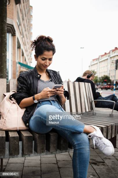 Smiling woman using mobile phone while sitting on wooden bench in city