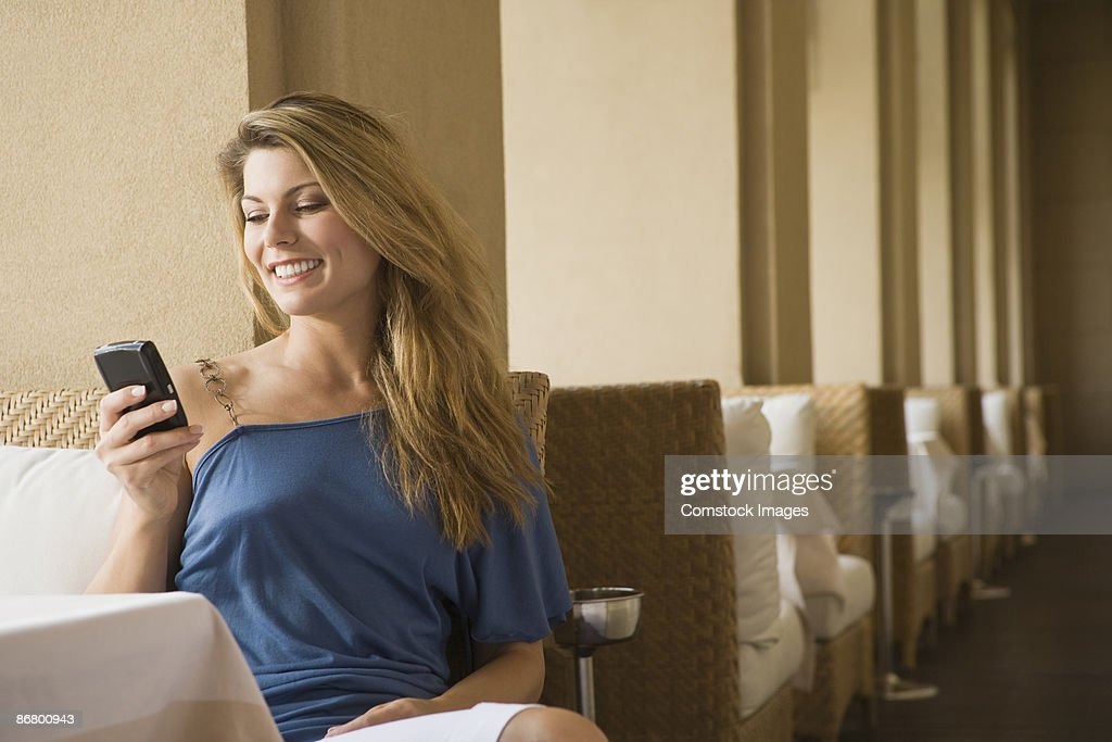 Smiling woman using PDA in restaurant : Photo