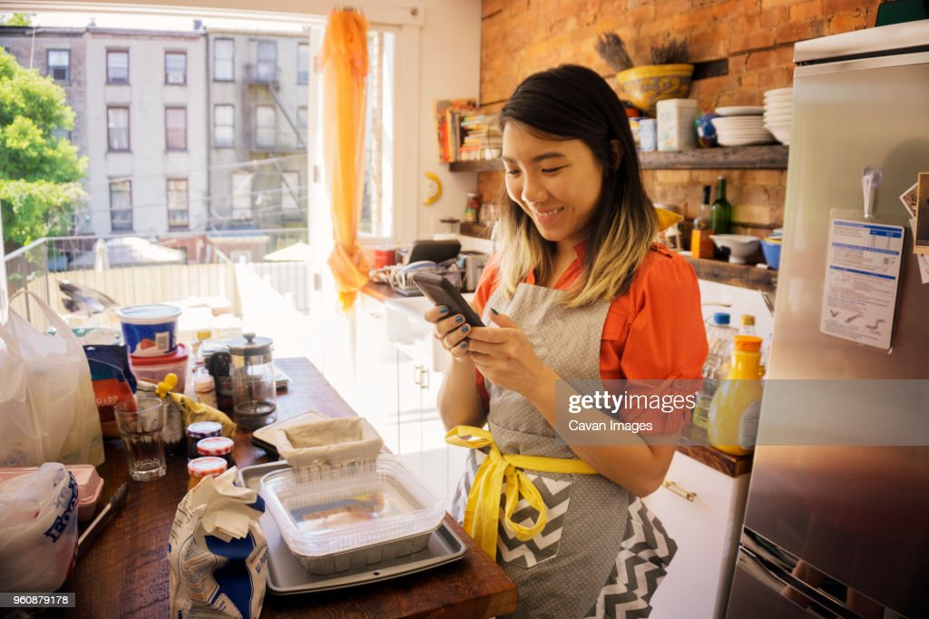Smiling woman using phone while cooking in kitchen at home : Stock Photo