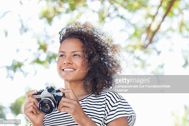 Smiling woman using retro camera outdoors