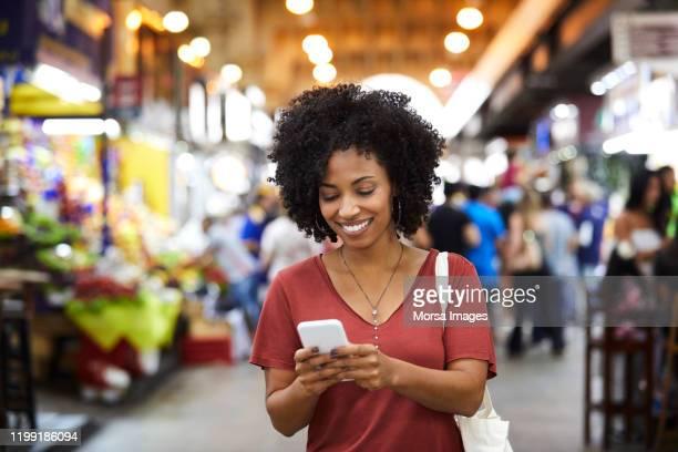 mulher de sorriso que usa o telefone esperto no supermercado - smartphone - fotografias e filmes do acervo
