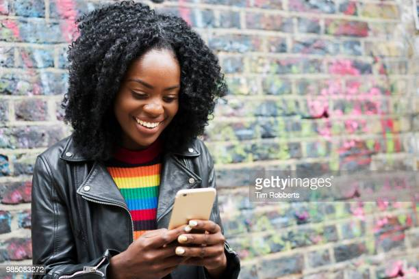 Smiling woman using smart phone next to colourful wall.