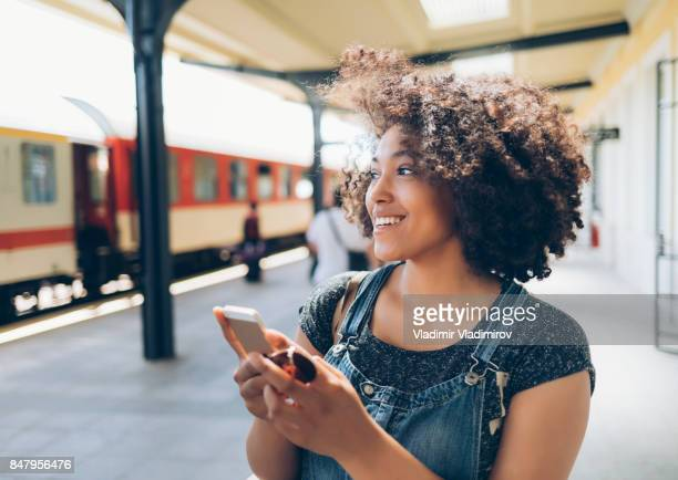 smiling woman using smart phone on station - estação imagens e fotografias de stock
