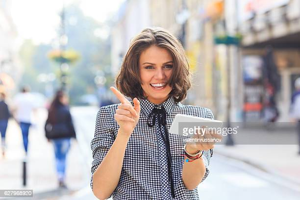 Smiling woman using smart phone on street