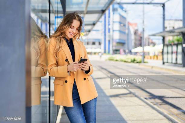 smiling woman using smart phone while waiting at tram station - leaning stock pictures, royalty-free photos & images