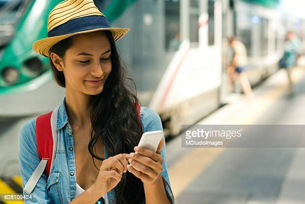 Smiling woman using smartphone at the subway station.