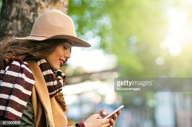 smiling woman using smartphone. - brown hat stock photos and pictures