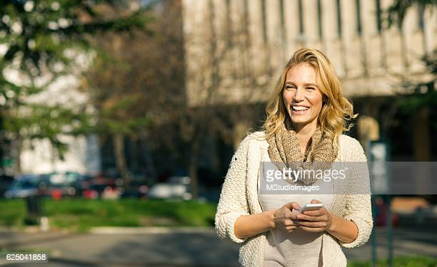 Smiling woman using smartphone,