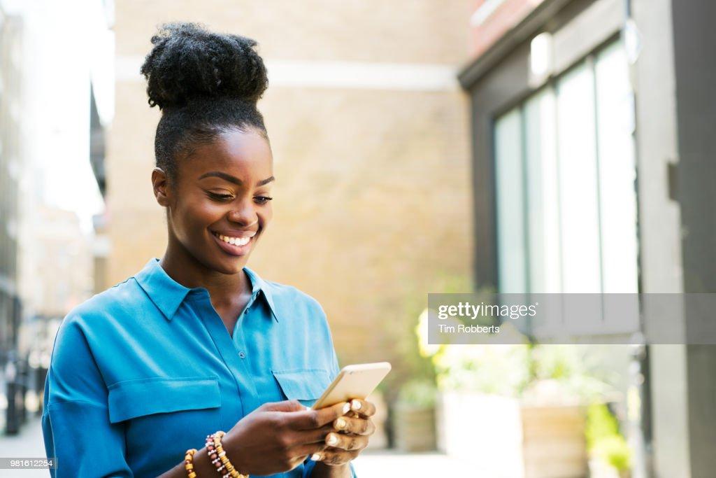 Smiling woman using smartphone : ストックフォト