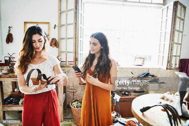 smiling woman using smartphone to take picture of shoe while shopping with friend in boutique - hi tech moda stock pictures, royalty-free photos & images