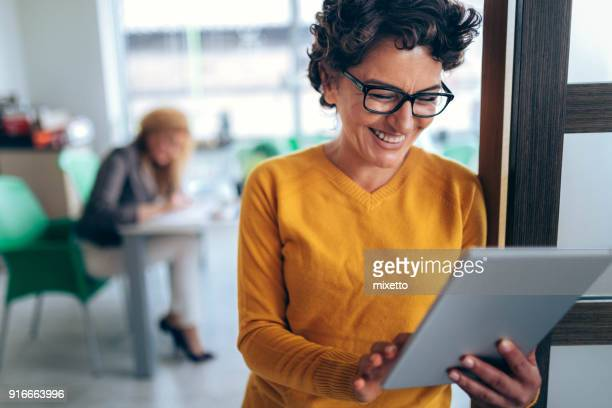 smiling woman using tablet in the office - businesswear stock pictures, royalty-free photos & images