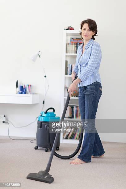 Femme souriante de l'aspirateur salle de séjour