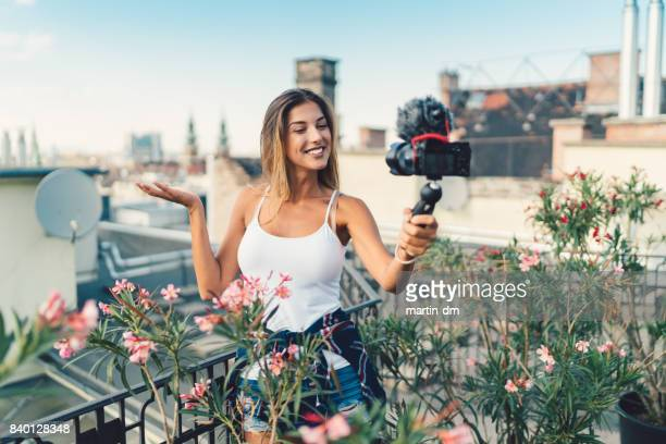Smiling woman vlogging at rooftop terrace